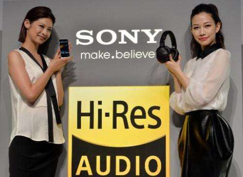 Models display Japanese electronics giant Sony's digital audio player 'Walkman ZX-1' (L) and headphones 'MDR-1', as Sony unveils