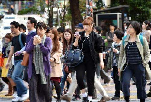 Pedestrians use their smartphones on a street in Tokyo, November 3, 2014. Growing ranks of cellphone addicts are turning cities