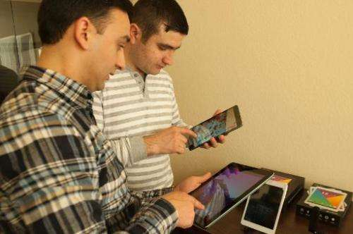 People check out Armenia's first tablet computers, ArmTabs, designed by the joint Armenian-US company Minno, in Yerevan, on Marc