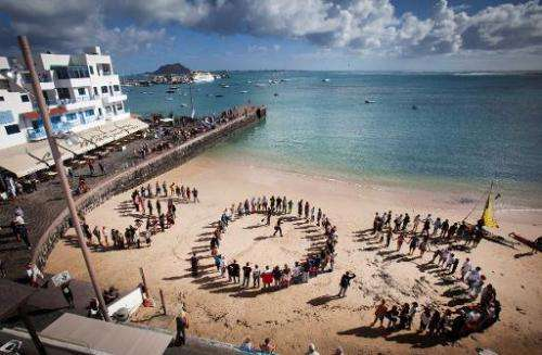 People form a giant S.O.S. on a beach as they protest against oil exploration being carried off the coast of the Canary Islands,