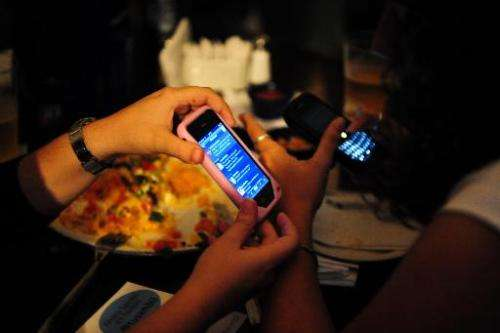 People use smartphones in Caracas, April 27, 2010