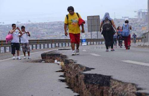 People walk along a cracked road in Iquique, northern Chile, a day after a powerful 8.2-magnitude earthquake hit off Chile's Pac