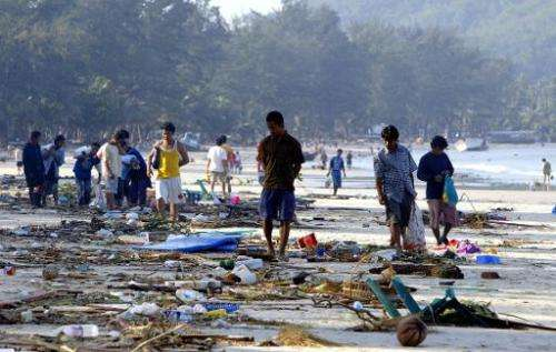 People walk through debris on Pathong beach on Phuket island, southern Thailand, on December 27, 2004, a day after a tidal wave