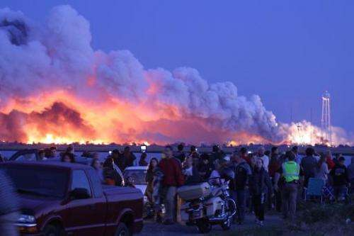People who came to watch the launch walk away after an unmanned rocket owned by Orbital Sciences Corporation exploded (backgroun