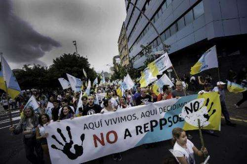 "Protestors carry a banner saying ""We live here, we decide here"" during a demonstration against oil exploration, on the"