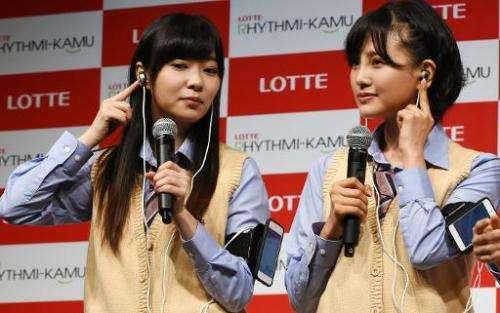 Rino Sashihara (L) and Haruka Kodama, members of pop group HKT48, display Lotte's prototype 'Rhythmi-Kamu', ear phones that coun