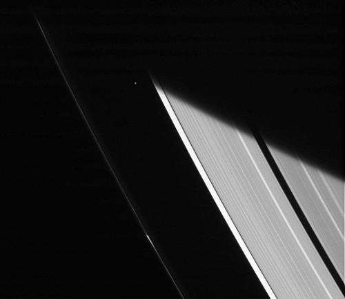 Saturn's moon Atlas shines between gas giant's rings