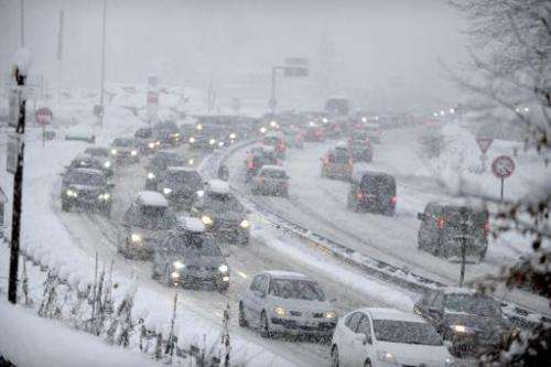 Snow fall as cars move bumper-to-bumper along the motorway near Albertville, on December 27, 2014, as they make their way into t