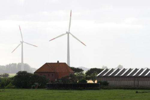 Solar cells are seen along windmills at a farm on the Pellworm island in northern Germany, on August 9, 2013