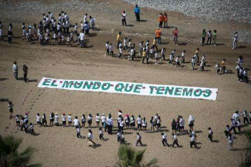 Some 700 Peruvian children form a large image of a tree at Lima's Miraflores beach to send a message about climate change on the