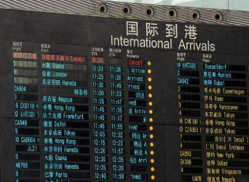 The arrival board shows the missing Malaysia Airlines flight (top, in red) as 'cancelled', at Beijing International Airport, on