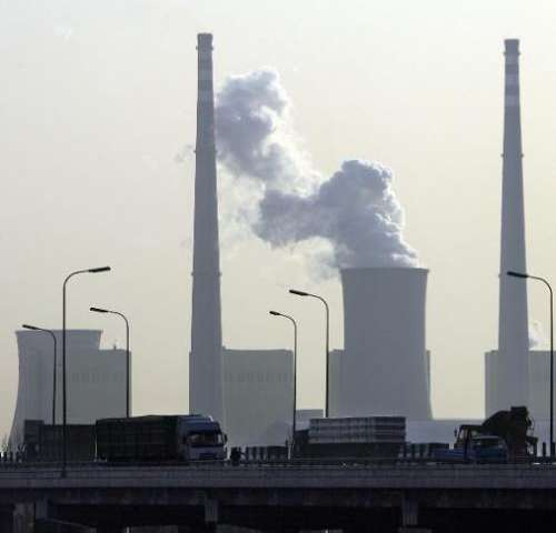 Towering smokestack chimneys and a cooling tower emit steam clouds into the air on November 30, 2006 in Beijing