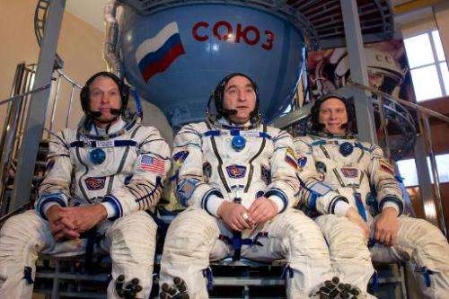 US NASA astronaut Steven Swanson (L) sits together with Russian cosmonauts, Alexander Skvortsov (C) and Oleg Artemyev in front o