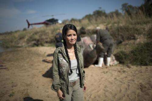 Vietnamese pop diva Hong Nhung, fights back tears as she stands near the carcass of a decomposing white rhino on the banks of a