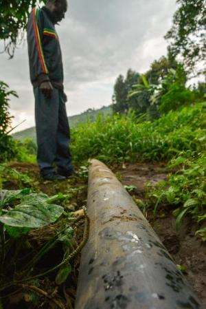 Villagers from Rugari in the Virunga National Park, eastern Democratic Republic of Congo look at a water pipe on June 17, 2014