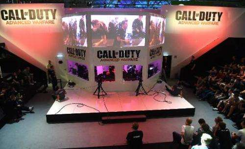"""Visitors to the """"Gamescom"""" fair play """"Call of Duty: Advanced Warfare"""" on August 14, 2014 in Cologne, Germany"""