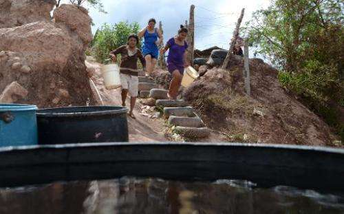 Women walk to collect water after a tanker filled containers in a poor neighbourhood on the outskirts of Tegucigalpa on August 7