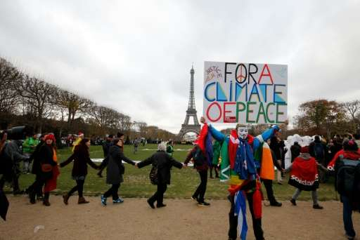 """A demonstrator wearing a mask of the Anonymous group holds a banner reading """"For a climate of Peace"""" during a rally ca"""