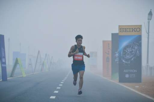 A participant runs through smog on Rajpath during the Airtel Delhi Half Marathon 2015 in New Delhi on November 29, 2015