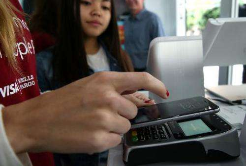 A worker demonstrates Apple Pay inside a mobile kiosk sponsored by Visa and Wells Fargo to demonstrate the new Apple Pay mobile