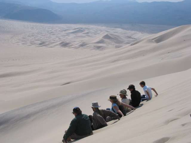 Physics of booming and burping sand dunes revealed