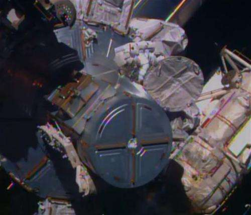 Spacewalking astronauts route cable in 1st of 3 jobs