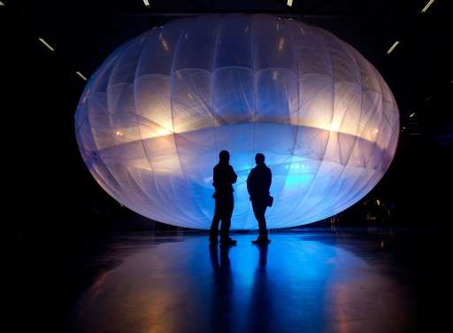 Visitors stand next to a a Google Project Loon balloon, on display at the Airforce Museum in Christchurch on June 16, 2013