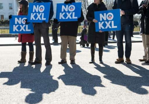 Demonstrators hold signs against the proposed Keystone XL pipeline from Canada to the Gulf of Mexico in front of the White House