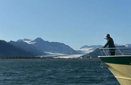 US President Barack Obama points to Bear Glacier during a boat tour of the Kenai Fjords National Park on September 1, 2015, as p