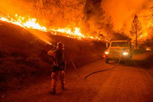 A firefighter douses flames from a backfire while crews continue battling a blaze near San Andreas, California, on September 12,
