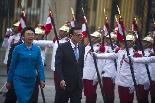 China's Prime Minister Li Keqiang (R) arrives with his wife Cheng Hong at the presidential palace in Lima to hold a meeting with