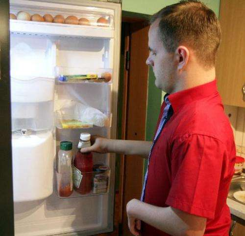 Martynas Girulis uses his new bionic arm to take a bottle of ketchup out of the fridge at his home in Pagegiai, Lithuania