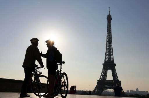 Picture taken early in the morning on September 27, 2015 shows two men with bikes chatting in front of the Eiffel Tower before t
