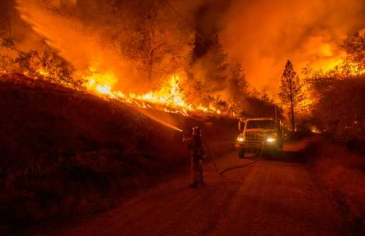 A firefighter douses flames from a backfire while battling the Butte fire near San Andreas, California on September 12, 2015
