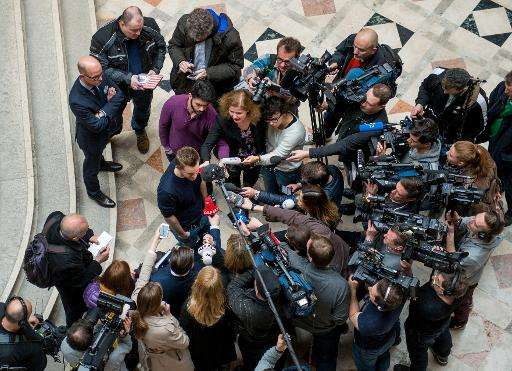 Austrian activist Max Schrems talks to journalists in the courthouse after officially filing a suit against Facebook in Vienna o