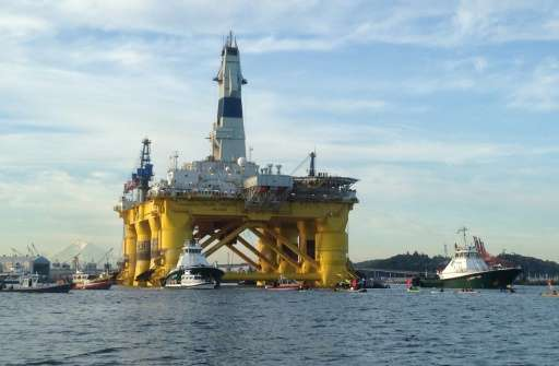 """Greenpeace activists in kayaks try to block the departure of the Shell Oil """"Polar Pioneer"""" rig platform as it moved fr"""