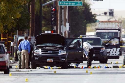 Investigators look at the vehicle involved in a shootout between police and two suspects in San Bernardino, California, on Decem