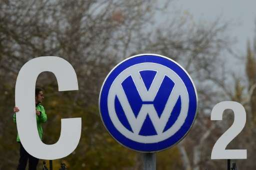 "Greenpeace activists form a ""CO2"" sign around the Volkswagen logo outside the company's headquarters in Wolfsburg, Ger"
