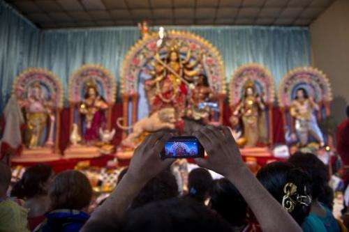 A Bangladeshi Hindu devotee takes photographs with his cell phone of the Durga pandal at the Dhakeshwari temple in Dhaka on Octo