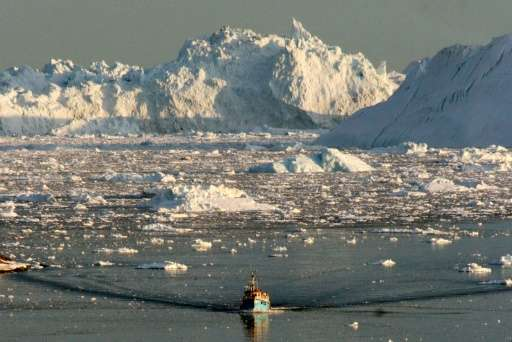A boat skims through the melting ice in the Ilulissat fjord on the western coast of Greenland