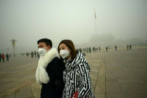 A couple walk through Tiananmen Square in Beijing during a heavy smog on December 1, 2015