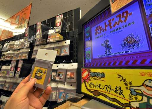 A customer picks up a used videogame software for Nintendo's Game Boy, at shop 'Super Potato' in Tokyo