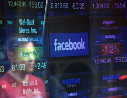 A Facebook logo seen through the windows of the NASDAQ stock exchange as people walk by in New York on May 17, 2012