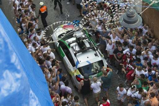 """A Google car passes revellers during the annual """"Tomatina"""" festivities in the village of Bunol, near Valencia on Augus"""