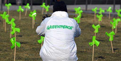 A Greenpeace activist sets miniature windmills in front of Strasbourg's railway station during an action aimed at increasing pub