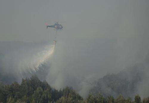 A helicopter fights a forest fire in the sector of Agua Santa, in Valparaiso, Chile on March 14, 2015
