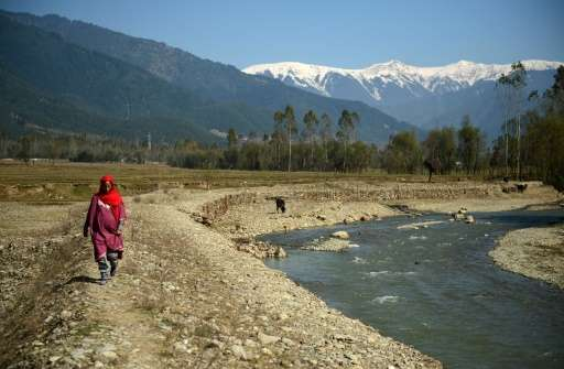 A Kashmiri villager walks past what used to be a pond holding drinking water in Lolab Valley in the foothills of the northern Ka