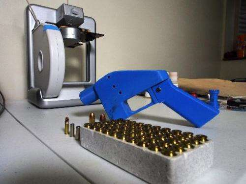 A Liberator pistol appears next to the 3D printer on which its components were made on July 11, 2013