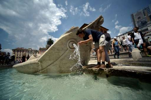 A man drinks fresh water from central Rome's Barcaccia fountain on June 30, 2015, as a major heatwave spreads through Europe
