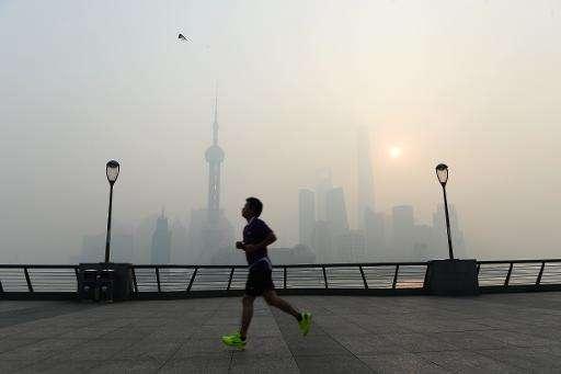 A man exercises amid heavy smog on the Bund in Shanghai on November 12, 2014